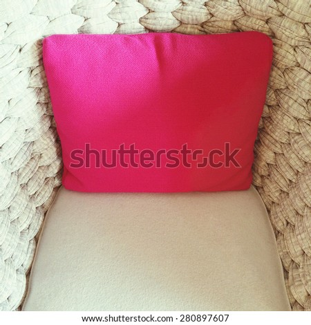 Bright pink cushion with decorating a beige armchair.