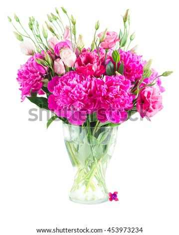 Bright pink peony and eustoma flowers bouquet in glass vase isolated on white background - stock photo