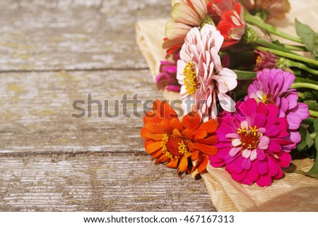 Bright pink, red, orange summer flowers on an old wooden surface. Summer background with flowers. Soft focus