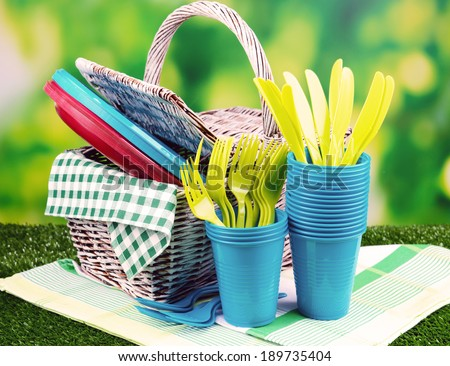 Bright plastic tableware on grass close-up - stock photo