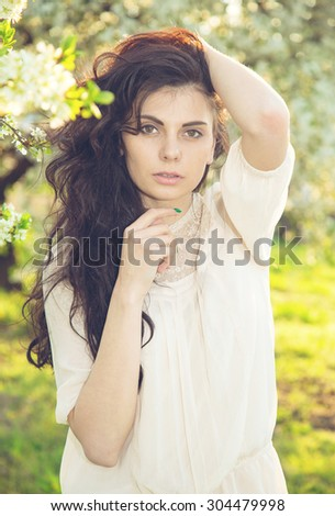 Bright portrait of a beautiful brunette woman in a flowering spring garden. Close up portrait of a beautiful brunette woman outdoors. Cute brunette woman posing in a park looking at camera. Life style