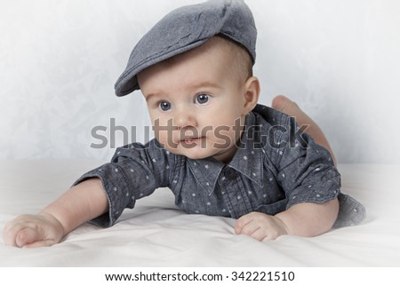 Bright portrait of adorable child in cap lying on his tummy  - stock photo