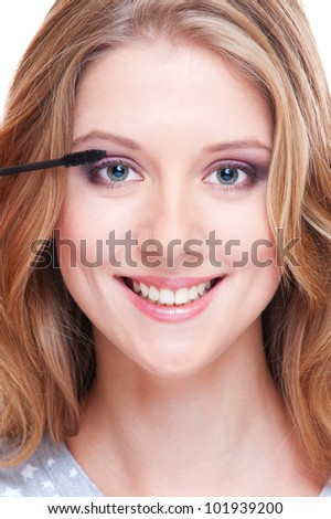 bright portrait of smiley woman applying make up