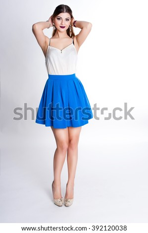 Bright positive fashion studio portrait of pretty young girl with purple lips, bright make up, sexy body, stylish trendy outfit: blue skirt, smart casual, cute emotions, color pop, white background. - stock photo