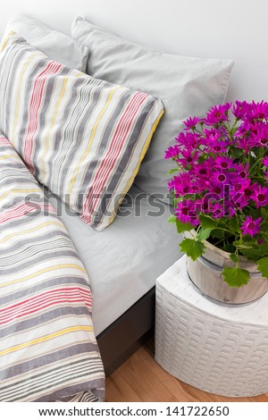 Bright purple flowers decorating a modern bedroom with striped bed linen. - stock photo