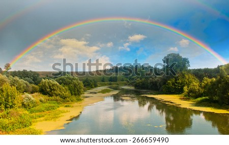 Bright rainbow in the sky with clouds above the forest and the river - stock photo