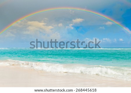 Bright rainbow in the sky with clouds above the sea - stock photo