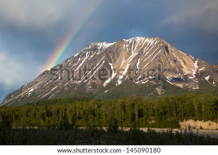 Bright rainbow shines over a rugged Alaskan mountain peak - stock photo