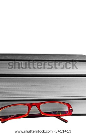 bright read glasses in-front of a stack of black and white books