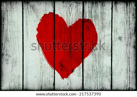 Bright red abstract love symbol on old wooden grunge wall - stock photo
