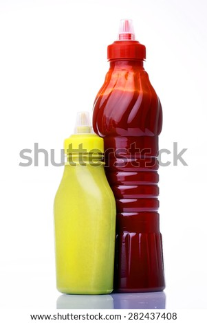 Bright red and yellow bottles of ketchup and mustard stand side by side on a white background, vertical photo - stock photo
