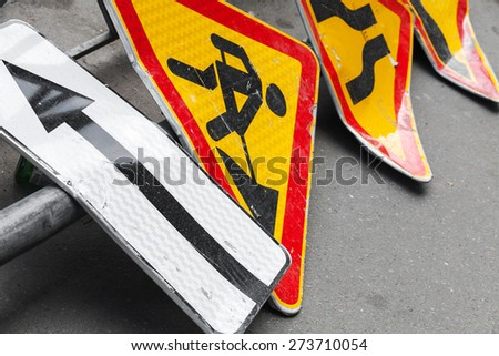 Bright red and yellow roadsigns lay on the asphalt road. Under construction and narrowing of the road marking - stock photo