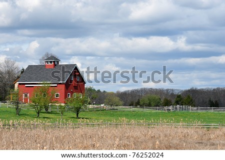 Bright red barn in Essex, Massachusetts, against a sky full of sullen looking clouds - stock photo