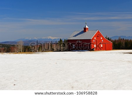 Bright red barn on a field of snow with the white mountains off in the distance. - stock photo