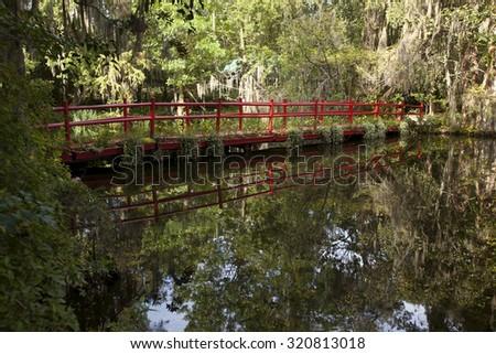 Bright, red bridge in the garden in Charleston, South Carolina - stock photo
