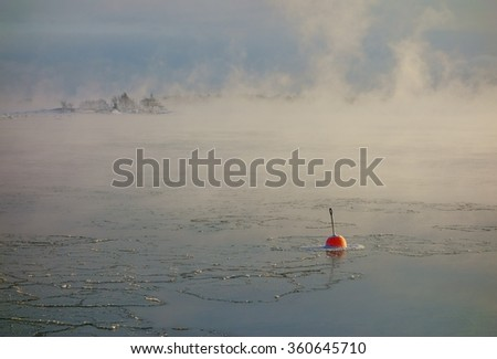Bright red buoy floating alone in the freezing Baltic Sea in Helsinki, Finland just hours before complete freeze over of the sea on an extremely cold January morning (-20C) on 6 January 2016.  - stock photo