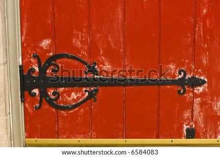 Bright red church doors with black ironwork.