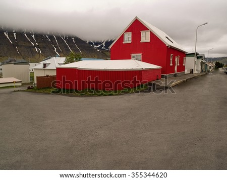 Bright red house on a street corner in front of a low lying cloud and fjord with streaks of snow in Isafjordur Iceland