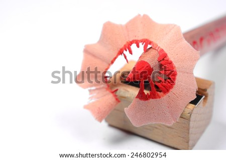 Bright red pencil with knife-sharpener and color wood shavings on a white background - stock photo