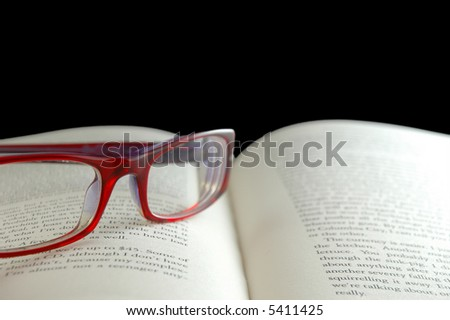 Bright red reading glasses on open book