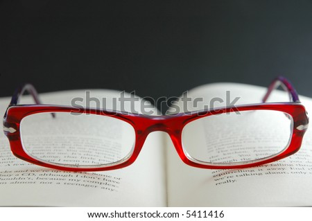 Bright red reading glasses on open book - focus on glasses - stock photo