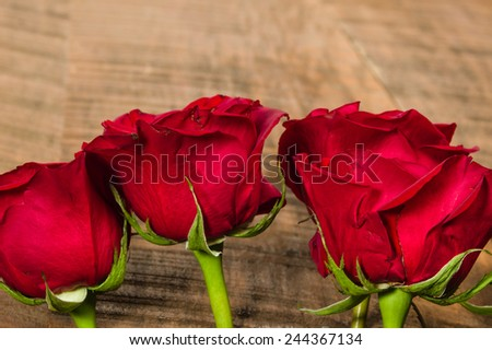 Bright red roses on a rough wooden table - stock photo