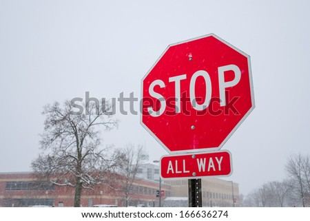 Bright red stop sign standing in a snowy day