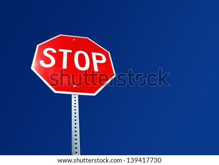 Bright red stop sign with blue sky background - stock photo