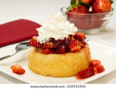 "Bright red strawberries topped with syrup and whipped cream on a yellow shortcake. Served on a square plate set on a white table cloth. Bowl of strawberries in the background.""strawberry shortcake"" - stock photo"