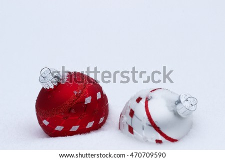 Bright red, white and silver Christmas ornaments buried in snow; holiday background with white copy space