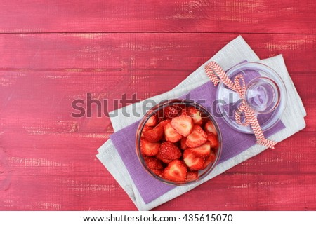 Bright red wooden background with glass pot of ripe sweet strawberry on purple and grey napkins. Copy space. Healthy and tasty food theme - stock photo