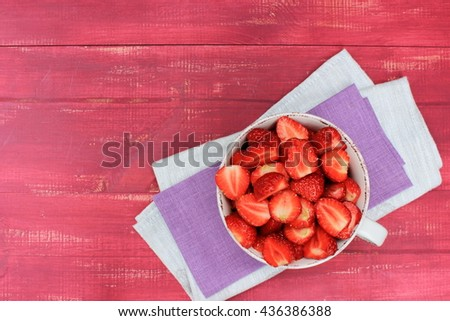 Bright red wooden background with large cup of ripe sweet strawberry on purple and grey napkins. Copy space. Healthy and tasty food theme - stock photo