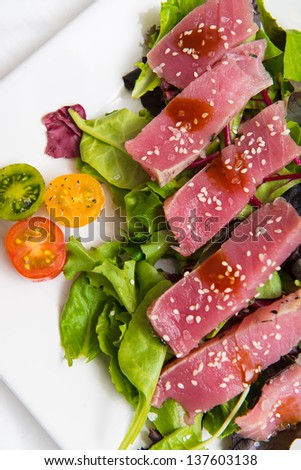 Bright red yellow fin sashimi tuna salad on white background - stock photo