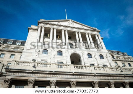 Bright scenic daytime exterior view of the imposing facade of the landmark Bank of England building in the City financial centre of London, England under bright blue sky