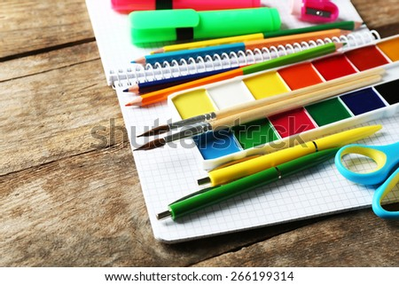Bright school stationery on old wooden table - stock photo