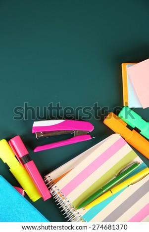 Bright school supplies on blackboard background - stock photo