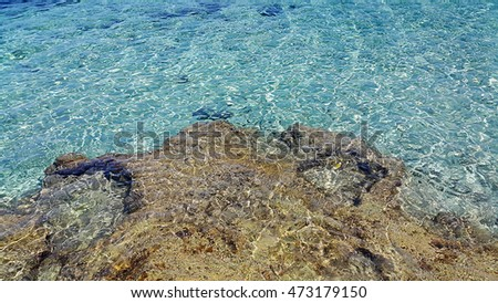 Bright sea water and coastal rocks nature background