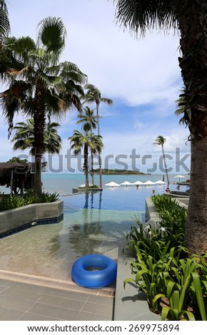 bright seascape with palm trees and a swimming pool during the day
