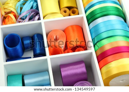 Bright silk ribbons in white wooden box, close up