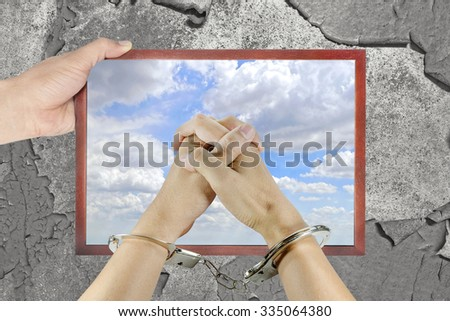 bright sky in a window frame with old wall background and Hand with  handcuffs - stock photo