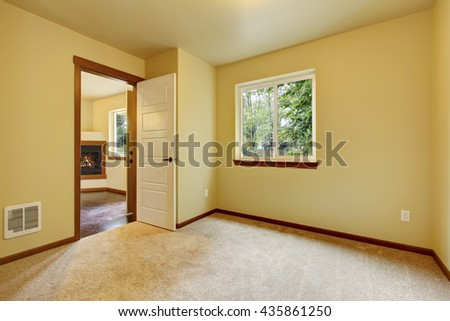Bright small empty room with carpet floor, one window and ivory walls. Door exit to the living room with fireplace. - stock photo