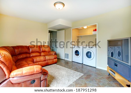 Bright small living room with brown leather couch, tv and cabinet. Room has a built-in laundry area with washer and dryer - stock photo