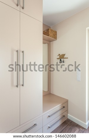 Bright space - an ecru classic wardrobe with a mirror - stock photo