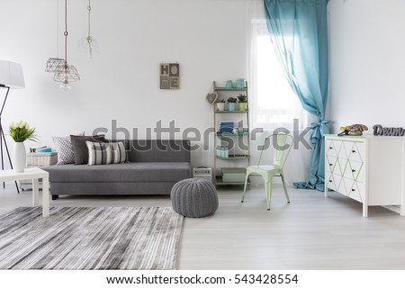 Bright spacious living room with comfortable couch and chest of drawers