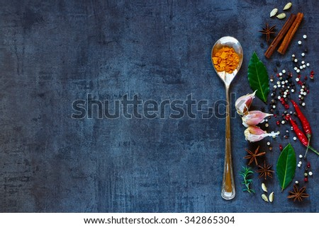 Bright spices on dark vintage background with space for text. Turmeric powder in old metal spoon with herbs and spices selection. Healthy eating and cooking concept. Top view. Dark rustic style. - stock photo