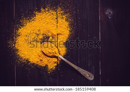 Bright spices, spilled curry powder and spoon fell on the wooden board - stock photo