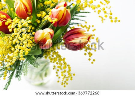 Bright spring bouquet of tulips and mimosa flowers on white