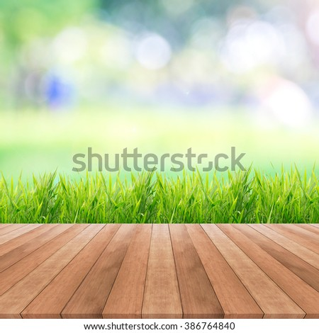 Bright spring grass field with sunlight bokeh background and wooden floor - stock photo