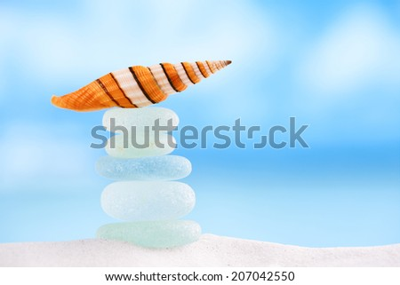 bright stripped sea shell with sea glass ocean , beach and seascape, shallow dof - stock photo