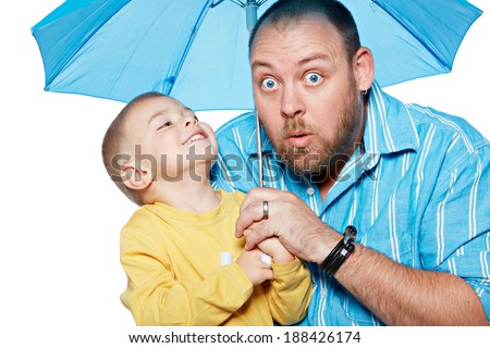 Bright studio portrait of young modern father and his small son under a blue umbrella on isolated white background - stock photo